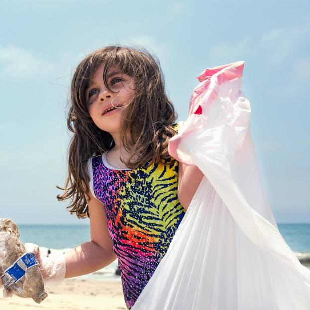 Von jungen Menschen lernen: Kind sammelt Müll am Strand ein