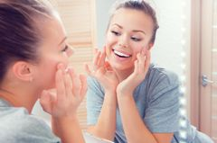 Dünne Haut: Frau schaut sich im Spiegel an