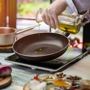 Öl zum Braten: Öl wird in eine Pfanne gegossen