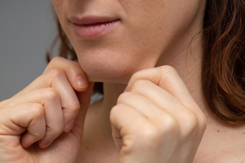 Schlaffe Haut: Frau fasst sich an schlaffe Haut im Gesicht