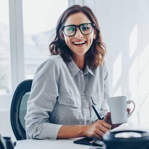 Lektor: Frau sitzt lächelnd am Laptop