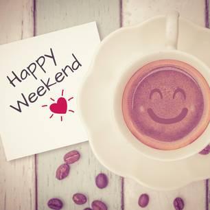 Horoskop: Ein Schild mit der Aufschrift Happy Weekend und eine Tasse mit lächelndem Kaffee