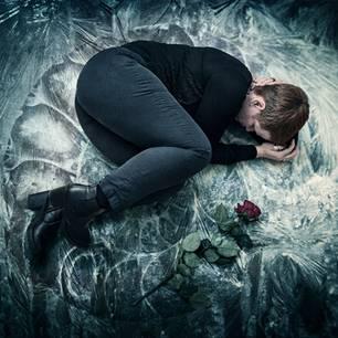 Gesichter der Depression: Frau liegt auf dem Boden