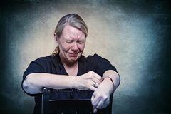 Gesichter der Depression: Frau sitzt auf Stuhl und weint