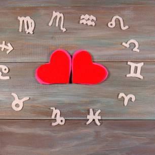 Holzsternzeichen um 2 rote Herzen