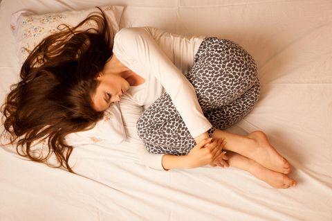 7 Perioden-Auffälligkeiten, die ein Warnzeichen sein können: Frau mit Unterleibschmerzen