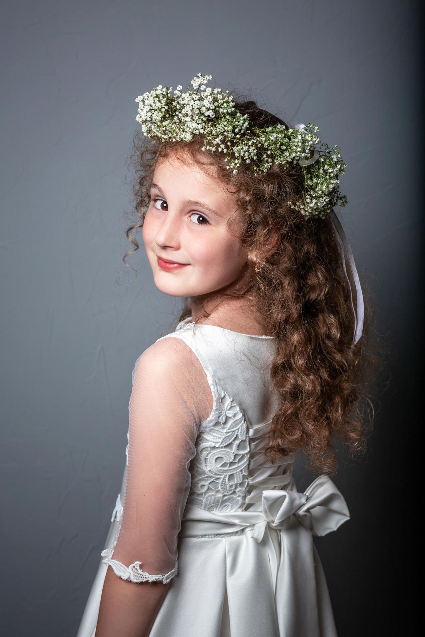 Kommunionsfrisuren: Mädchen mit Blumen im Haar