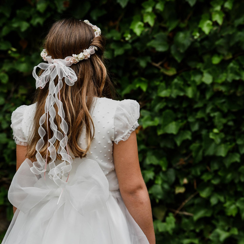 Kommunionsfrisuren: Mädchen mit Blumen- und Schleifenkranz im Haar