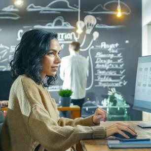 Mediengestalter: Frau sitzt am Computer und arbeitet