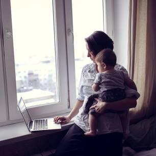 Frau am Laptop mit Kind auf Arm