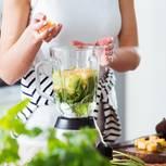 Frau befüllt Mixer mit frischem Obst