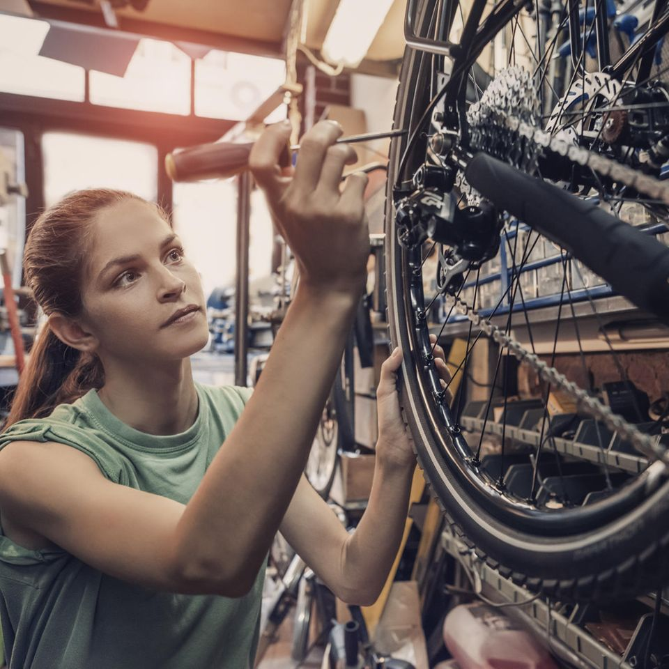Fahrradmonteur: Frau repariert ein Fahrrad