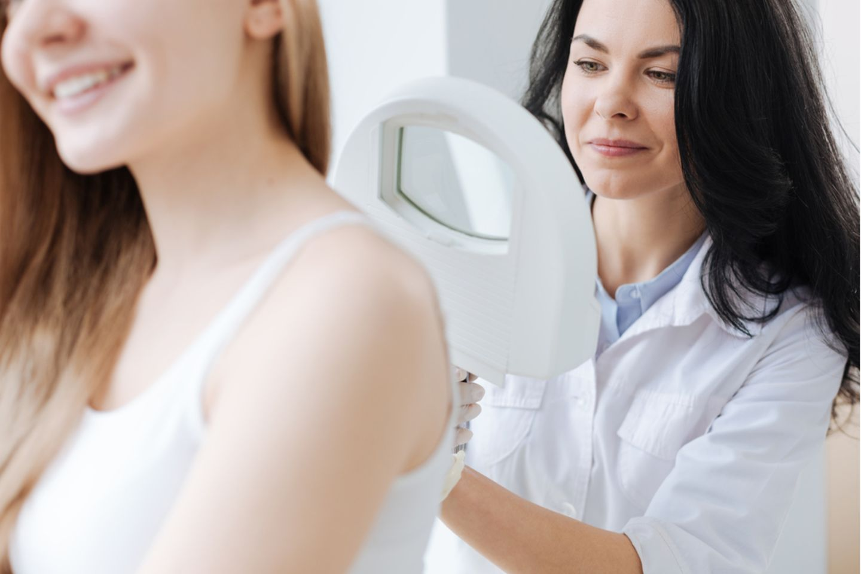 Dermatologe: Hautärztin mit Lupe