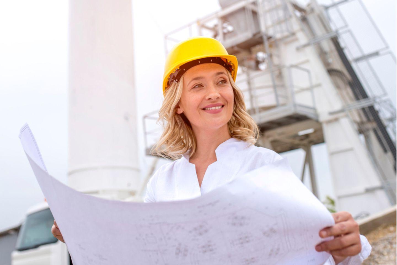 Bauingenieur: Ingenieuren mit Bauplan auf Baustelle