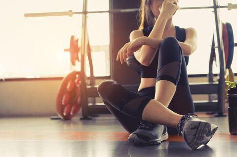 Frau sitzt auf dem Boden im Fitnessstudio