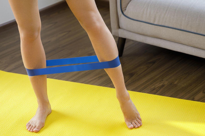 Frau trainiert zu Hause mit Fitnessband