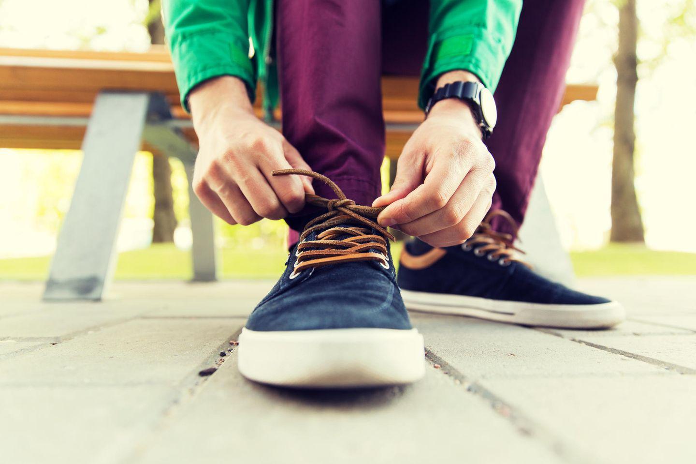 Mann bindet sich die Schuhe zu