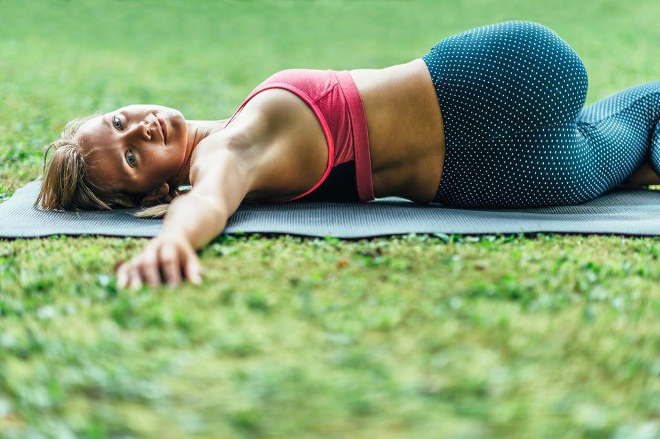 Was tun bei Rückenschmerzen?: Frau liegt gedreht auf Yogamatte