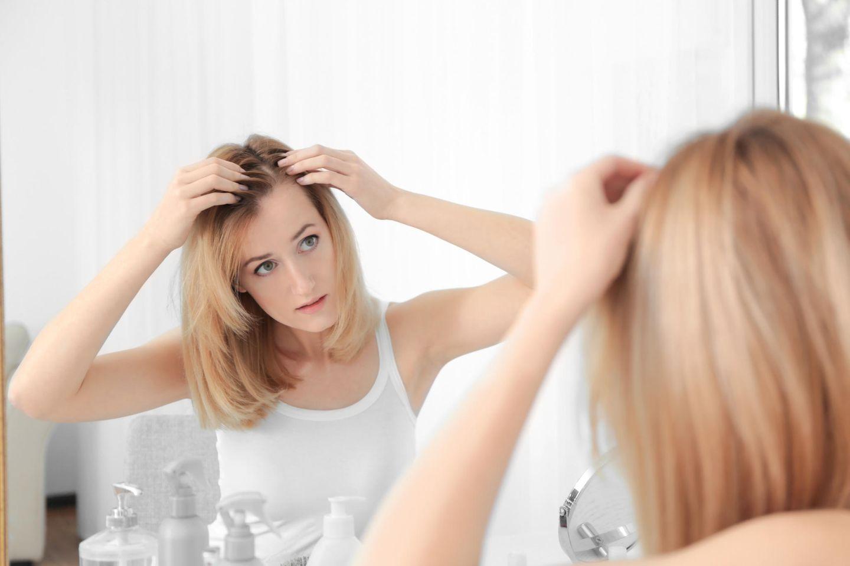 Koffein-Shampoo: Frau tastet Haar ab