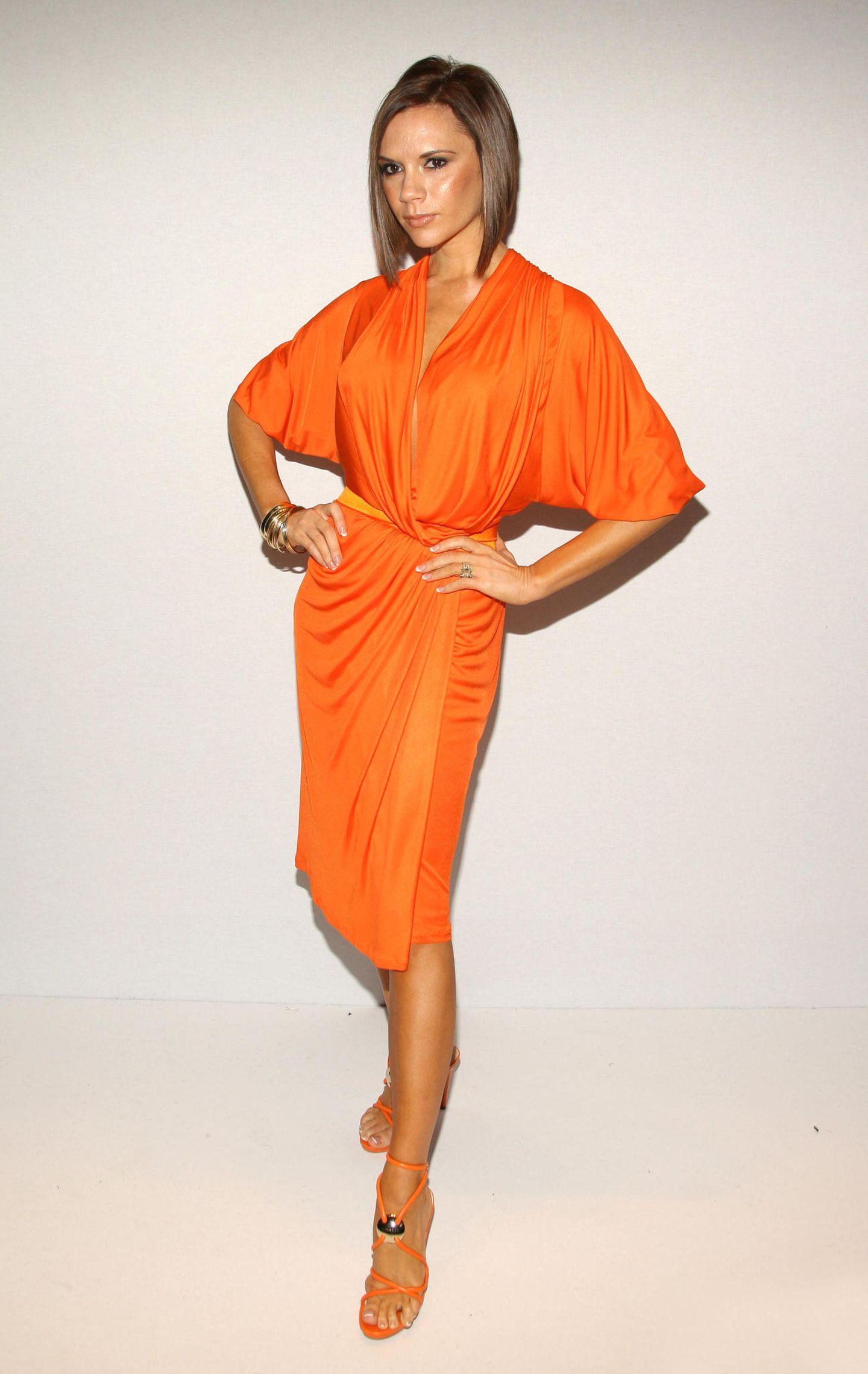 Victoria Beckham: im orangen Kleid