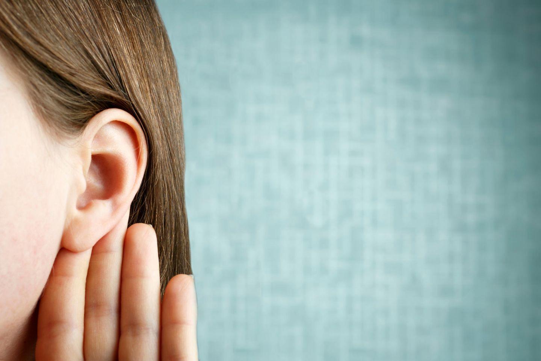 Frau hält sich die Hand ans Ohr
