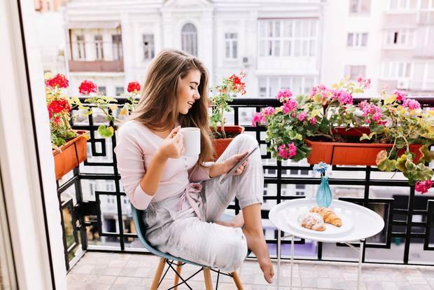 Balkon gestalten: Junge Frau sitzt auf Balkon
