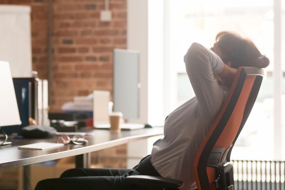 Bandscheibenvorfall: Frau sitzt auf Stuhl