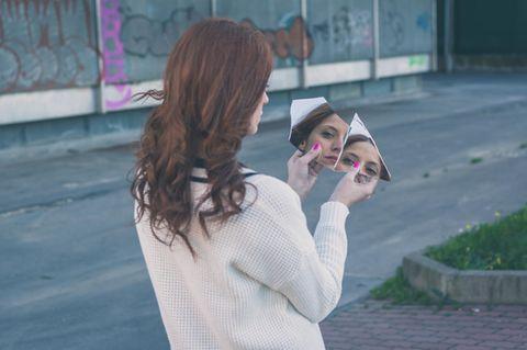 Selbstfindung: Eine Frau schaut in zwei Scherben eines zerbrochenen Spiegels