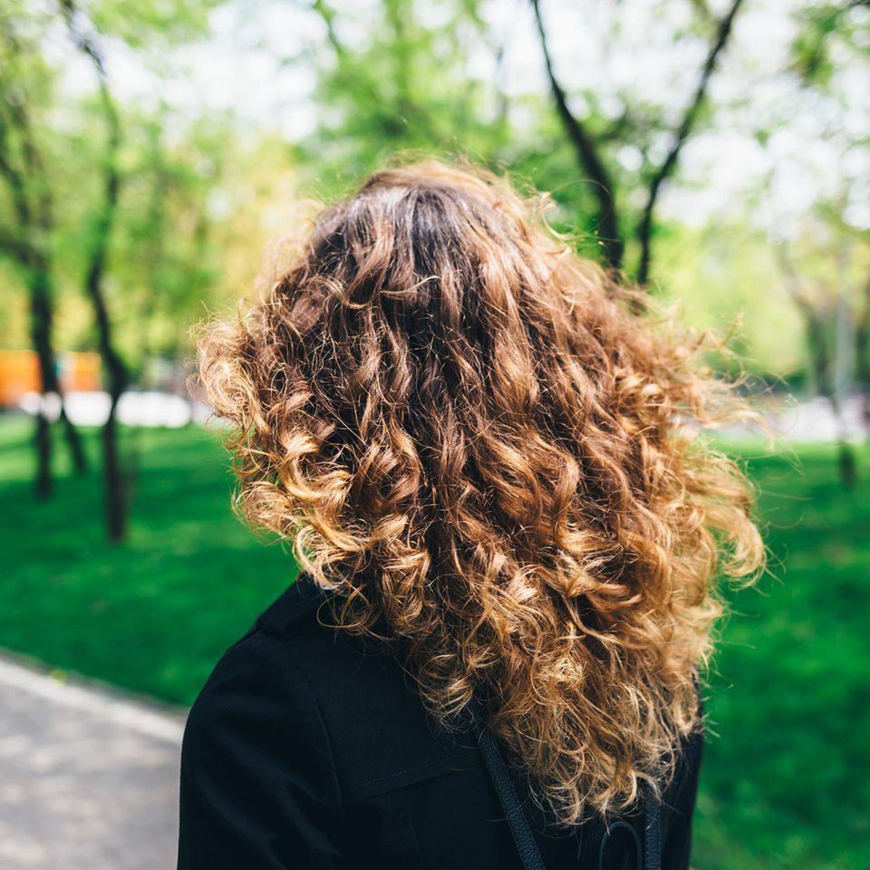 Frau mit langen Locken im Park
