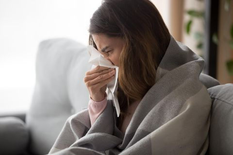 Frau putzt sich die Nase auf Sofa