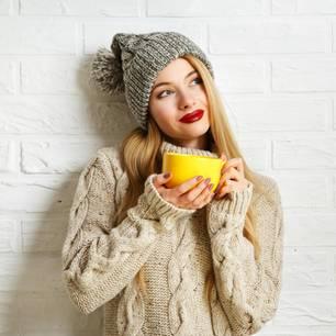Frau in Pullover und Mütze mit Tasse