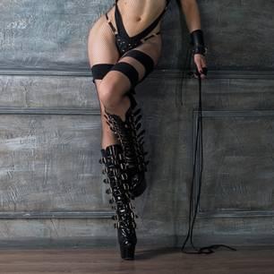 Dominante Frau in Plateauschuhen mit Peitsche