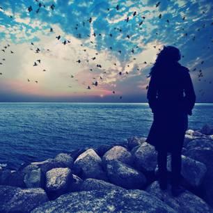 Frau schaut aufs Meer