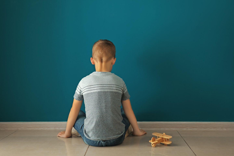 Kind mit Spielzeugflugzeug sitzt vor Wand
