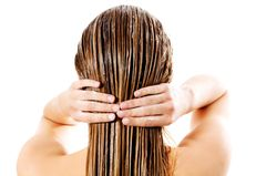 Frau, die Pflegemittel auf ihr Haar aufträgt