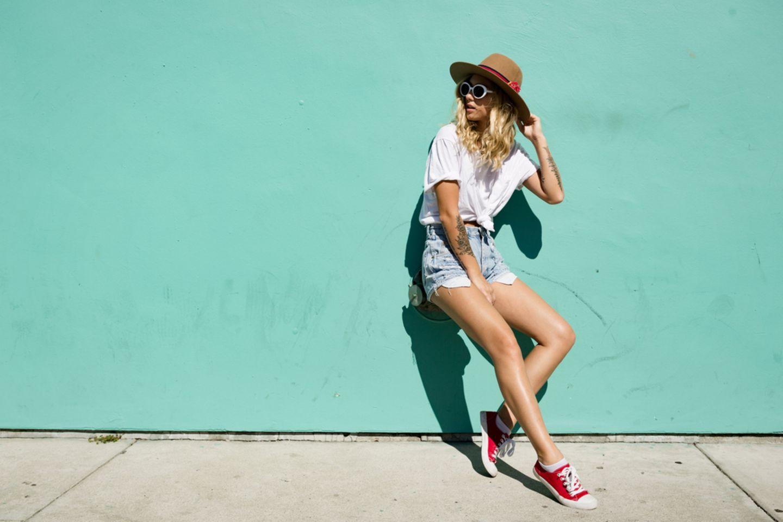 Leuchtturm-Tattoo: JUnge Frau steht an Wand gelehnt