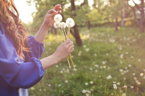Heuschnupfen: Frau mit Pusteblume