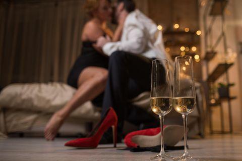 Paar auf Bett, Schuhe und Champagner im Vordergrund