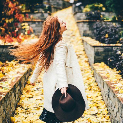 Rothaarige Frau im Herbst im Park
