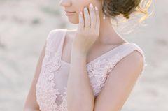 Frau in rosa Kleid mit Verlobungsring