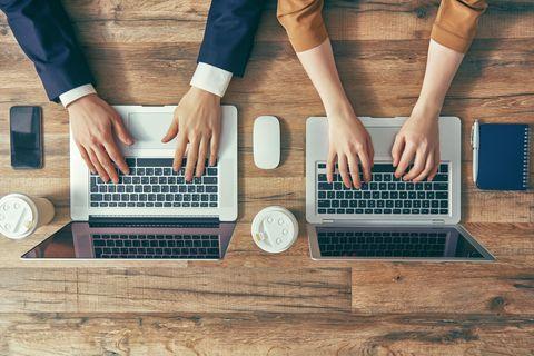 Mann und Frau nebeneinander an Laptops