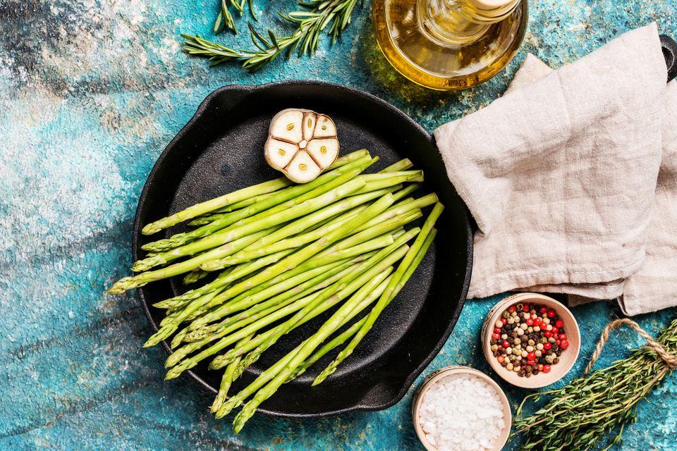 Gebratener grüner Spargel: Alle Zutaten in einer Pfanne auf blauem Grund