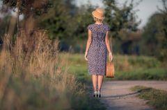 Frau in gepunktetem Kleid auf Weg