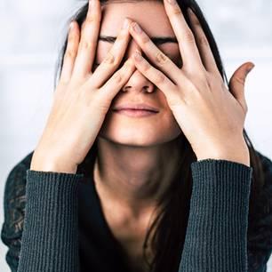 3 Tricks, um sich nicht mehr ständig ins Gesicht zu fassen: Frau mit Händen ins Gesicht