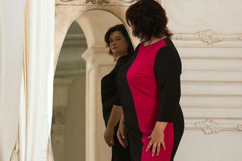 Frau mit Konfektionsgröße 40 sieht sich im Spiegel an