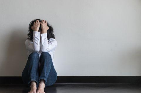 Frau mit Panikattacke sitzt auf dem Boden