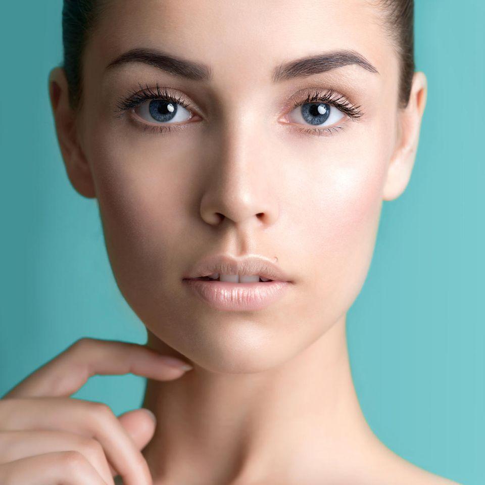 Frau mit perfekter Haut vor türkisem Hintergrund