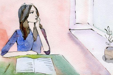 Horoskop: Eine Frau sitzt vor einem Buch und schaut nachdenklich aus dem Fenster