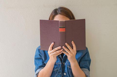 Frau hält Buch vor ihr Gesicht