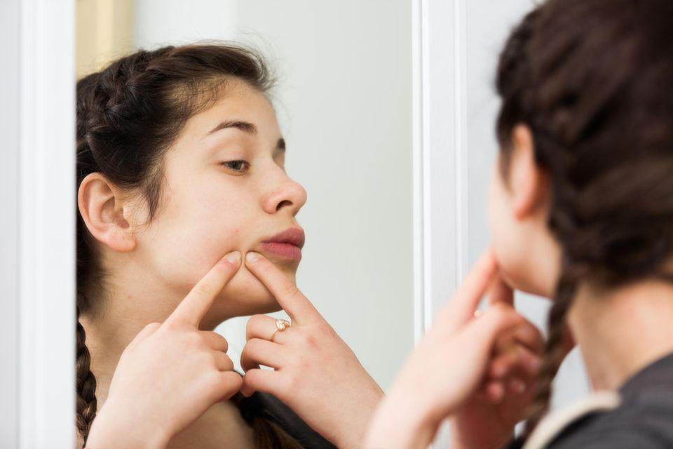 Aufgeschwollenes Gesicht: Frau kontrolliert unebene Stellen im Gesicht